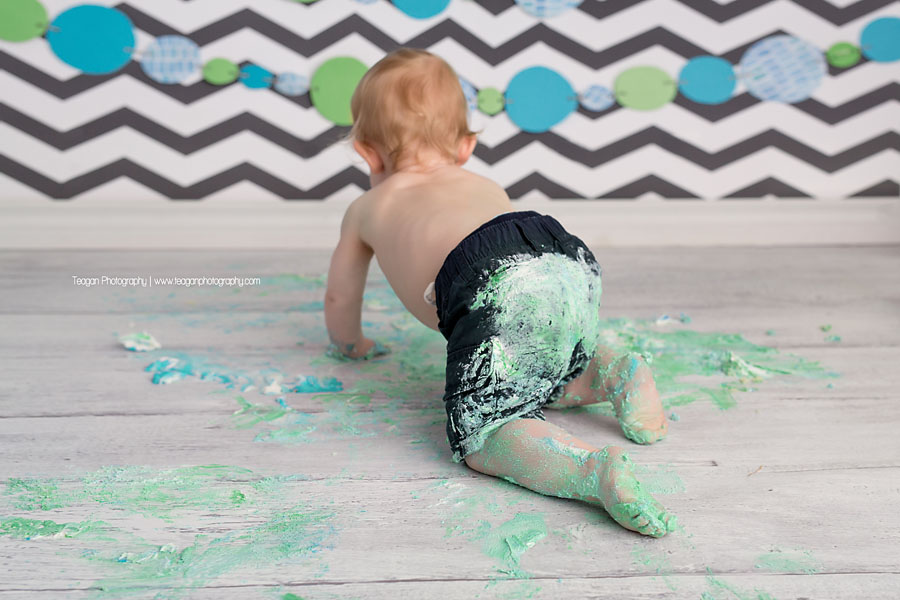 A blonde boy covered in icing crawls away during his Edmonton cake smash Photography session
