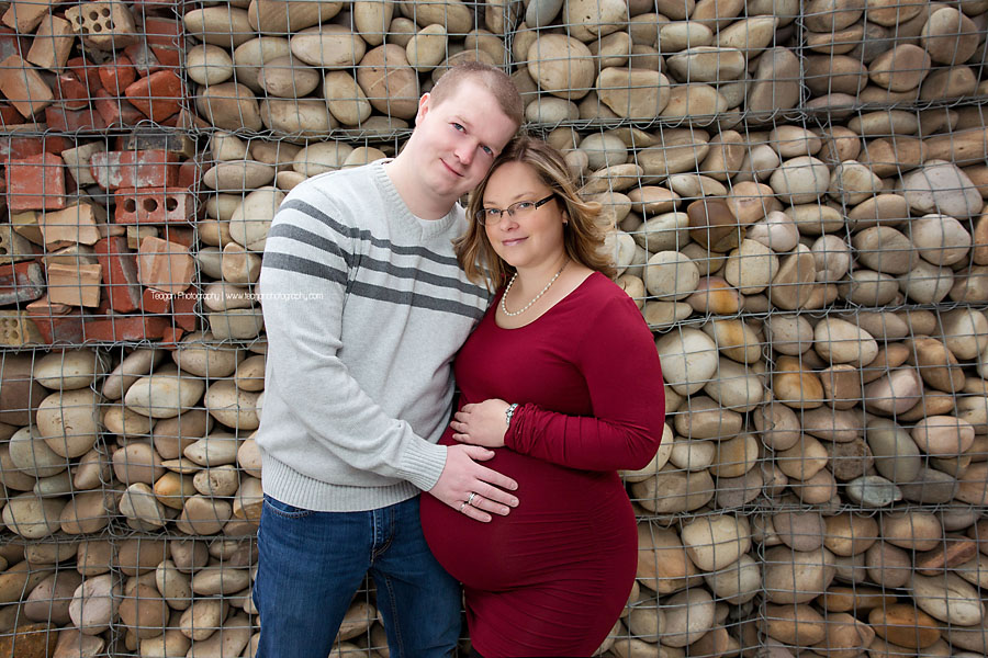 Wearing a burgundy coloured dress is a women hugging her belly during an Edmonton maternity photo shoot