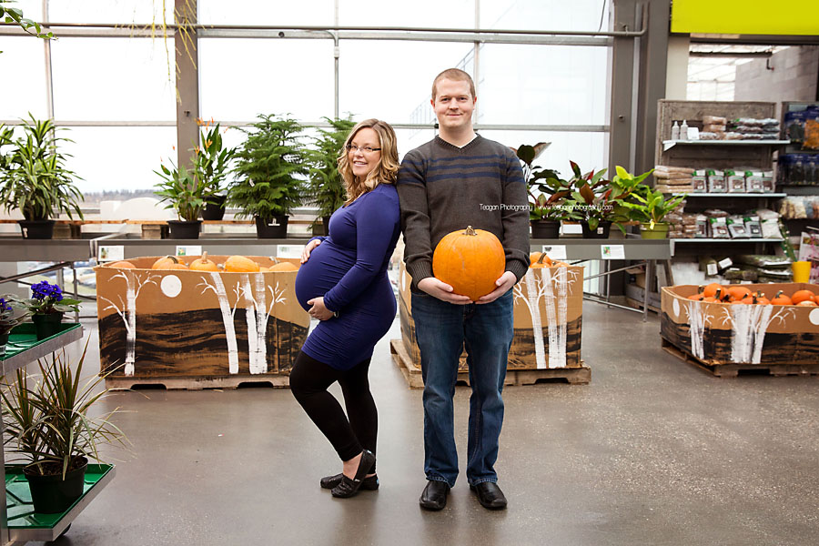 A husband holds a pumpkin next to his pregnant wife at the Enjoy Centre in St Albert during a maternity photoshoot