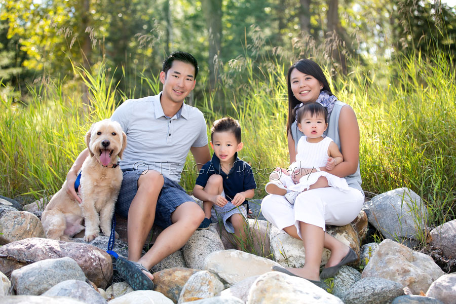 An Asian family poses together with their dog at Larch Sanctuary in Edmonton during family photos