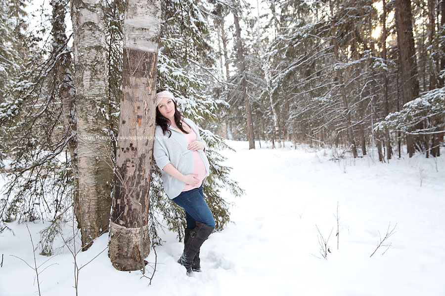 Wearing tones of pink and grey is an Edmonton woman hugging her pregnant belly in the snowy forests of Edmonton