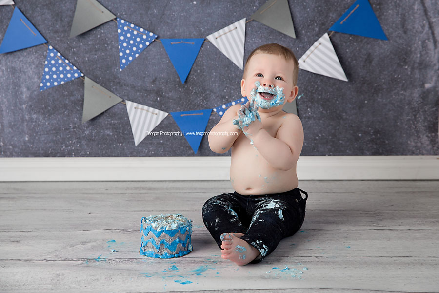 A one year old boy joyfully eats his blue iced cake during an Edmonton cake smash photography session
