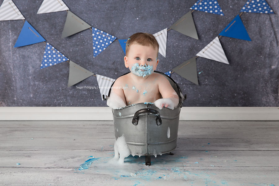 A birthday boy splashes in a metal bathtub after his Edmonton cake smash photo session