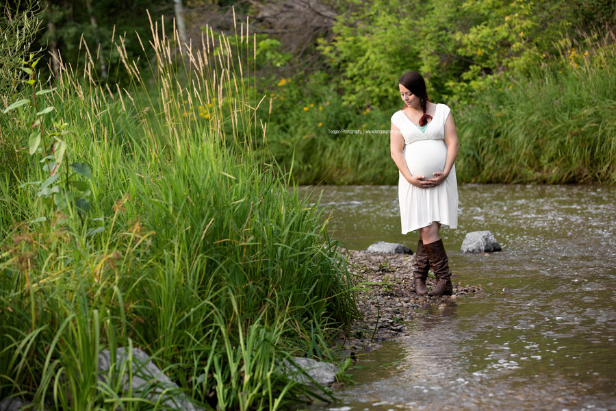 A pregnant Edmonton mother in a white dress poses during maternity photos in the Millcreek Ravine