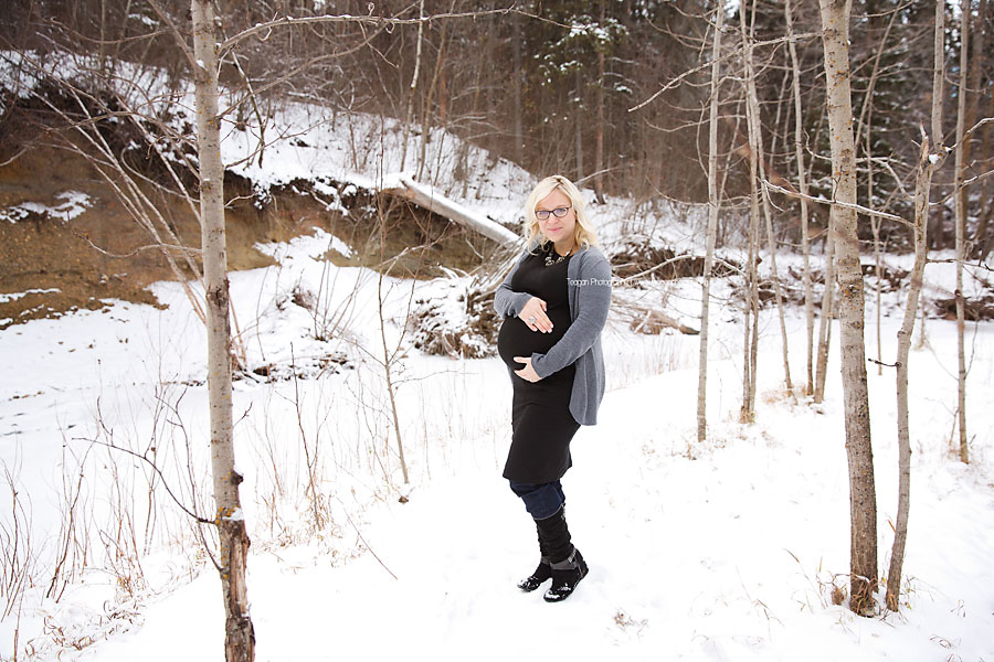 A pregnant woman with blonde haor stands in the snow during a winter maternity photography session in Edmonton