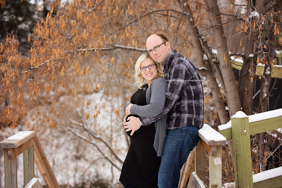 A blonde woman with dark rimmed glasses poses in front of dry orange leaves during a winter maternity session