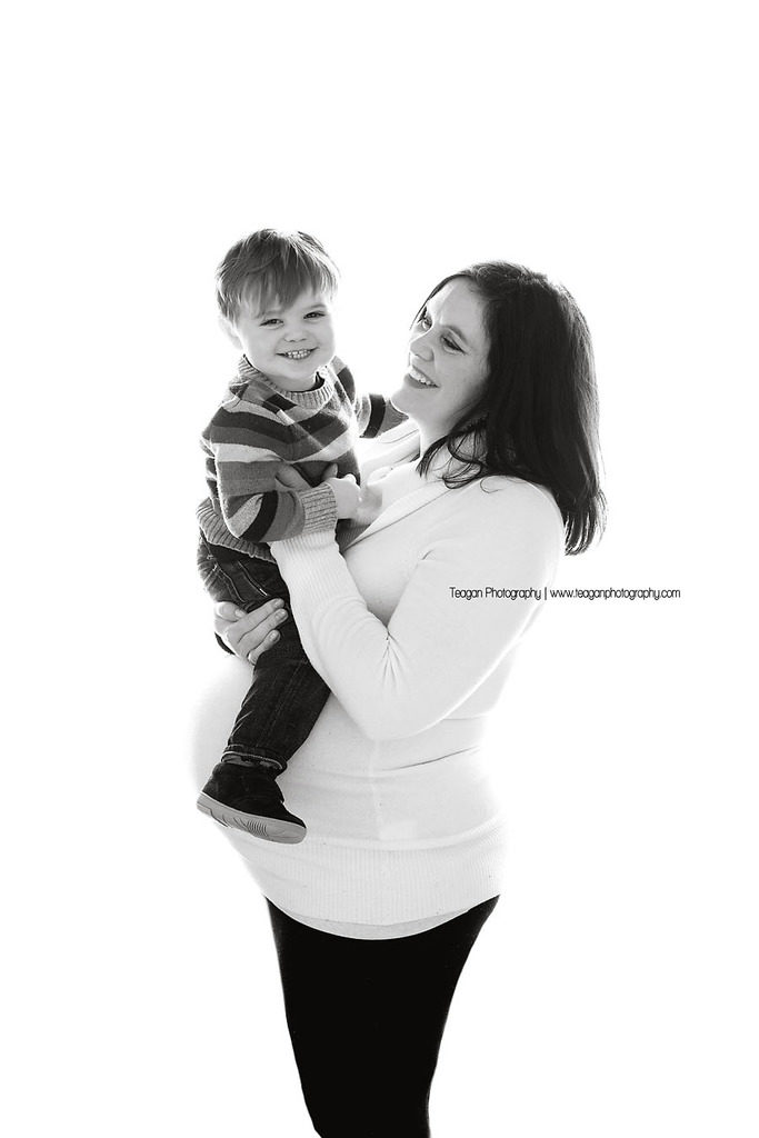 A burgundy haired mother wearing a white sweater poses for maternity photos at a top Edmonton studio