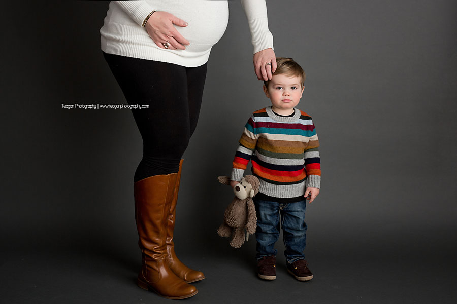 A mother brushed the hair out of her toddler son's eyes while holding her pregnant belly