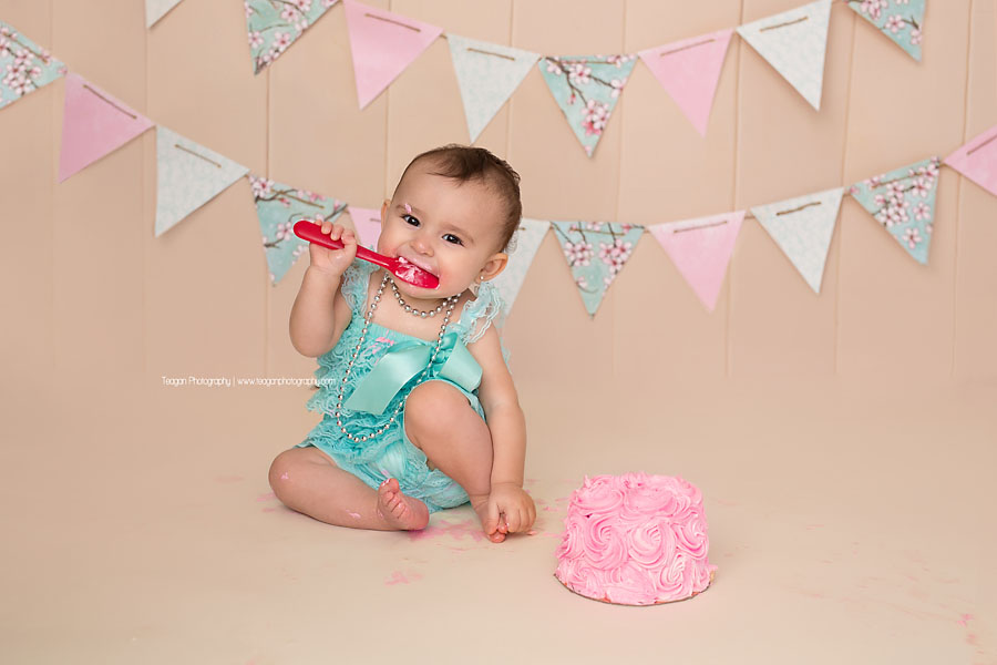 A one year old girl celebrates her first birthday with a pink and robin's egg blue cake smash in Edmonton