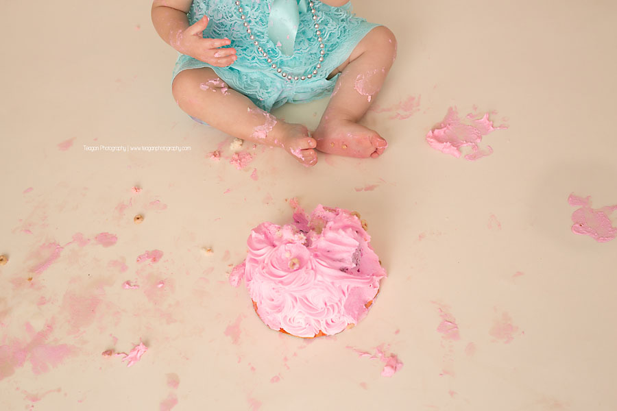 A close up photo of a one year old girl's toes  and her pink smash cake