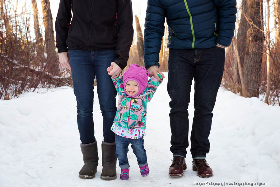 A one year old girl in her snowsuit laughs while walking with her parents