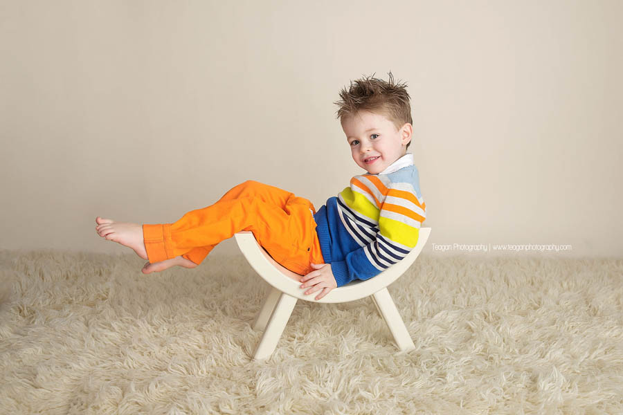 a little boy in orange pants and a striped sweater poses in a goofy way on a white curved bench during a photo shoot in Edmonton