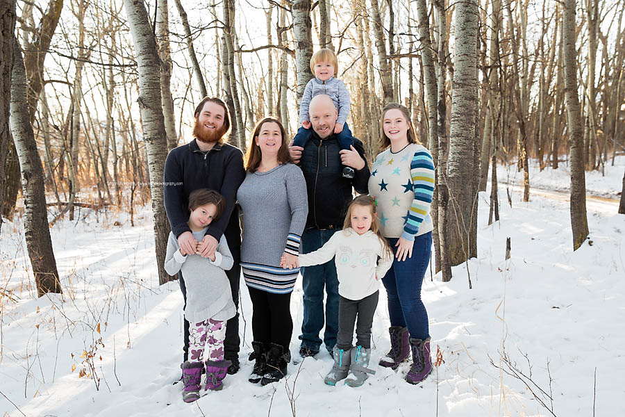 An extended family poses together in a sunlit poplar forest for winter photos in Edmonton.