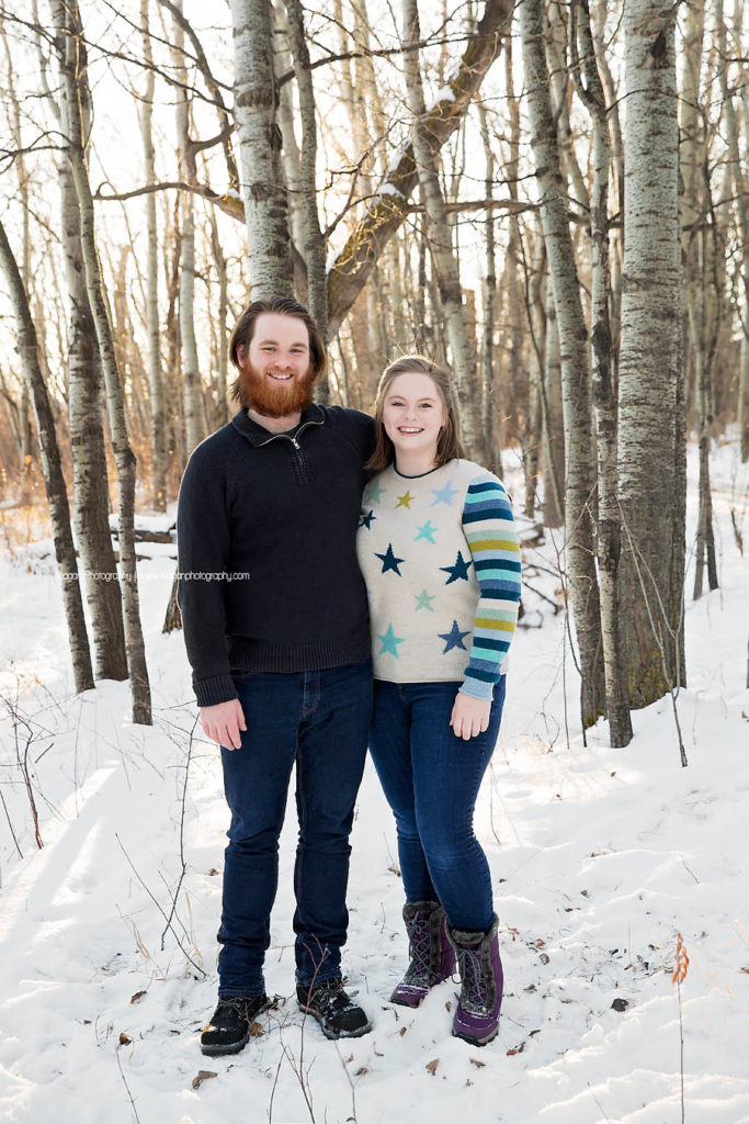 Adult siblings stand together in a winter forest during an Edmonton photo session