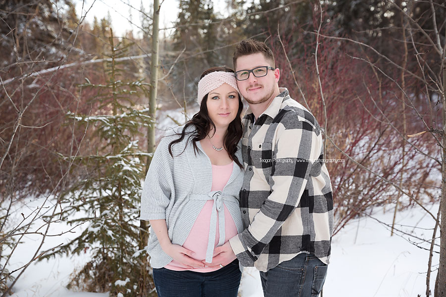 A husband and wife pose during a winter maternity photography session in Edmonton