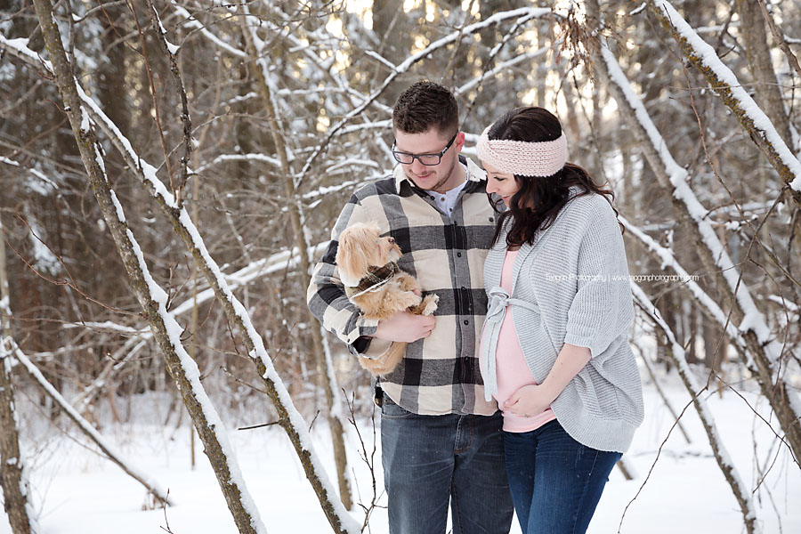 A pregnant couple poses with their terrier dog in the snow covered forests of Edmonton's River valley
