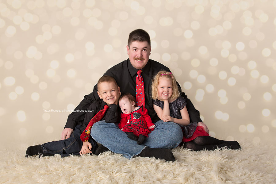 Dad sits on a cream rug with his twin children and new baby girl