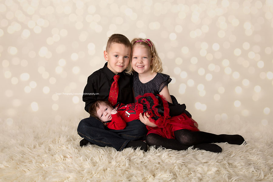 Twin children wearing red and black Christmas clothing hold their newborn sister during an Edmonton family photo shoot in the studio
