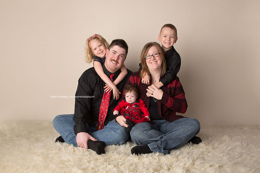 A family wearing black and red clothing sits together for a Christmas themed photoshoot in Edmonton