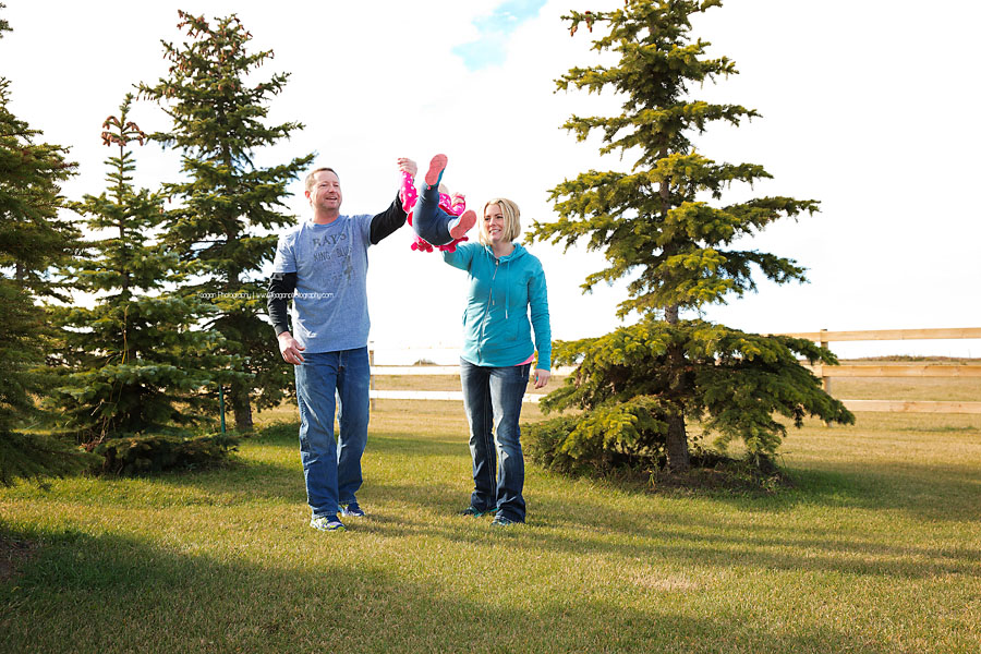 Parents play with their daughter in an Edmonton field