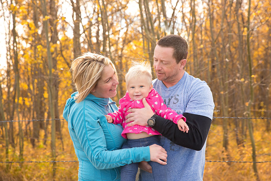 Mom and dad hug their one year old girl during a Fall photo shoot in Edmonton
