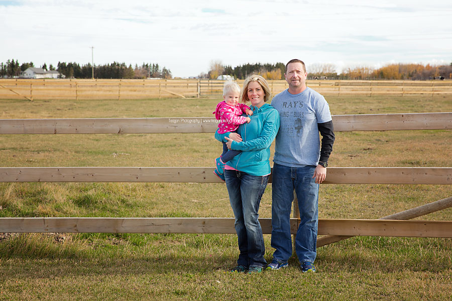A family poses next to a wooden farm fence during Fall photos in Edmonton