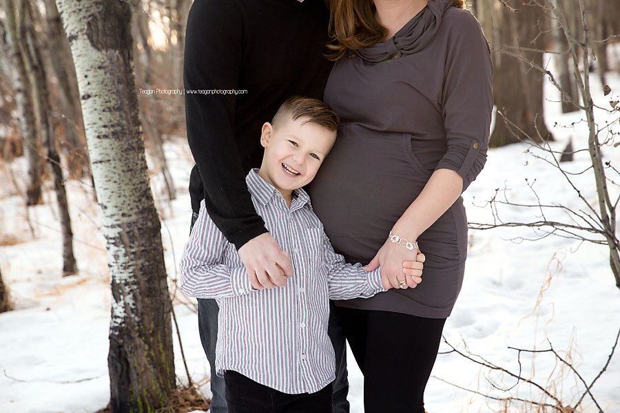 An elementary aged boy smiles while snuggling with his parents in a forest during an Edmonton Maternity Photography session