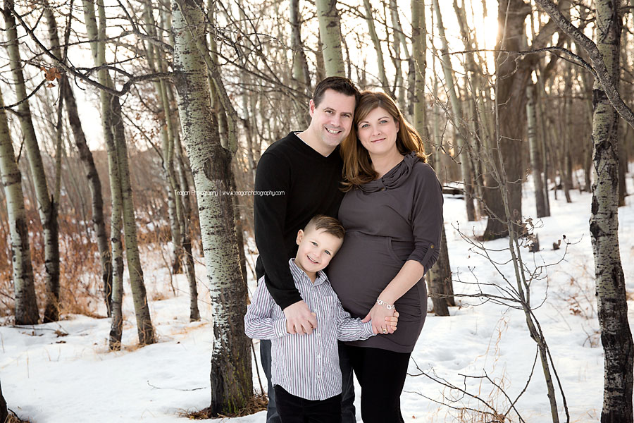 A family poses together in a winter forest in Edmonton