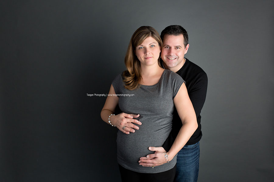 In front of a grey backdrop a couple poses for some studio maternity photo session