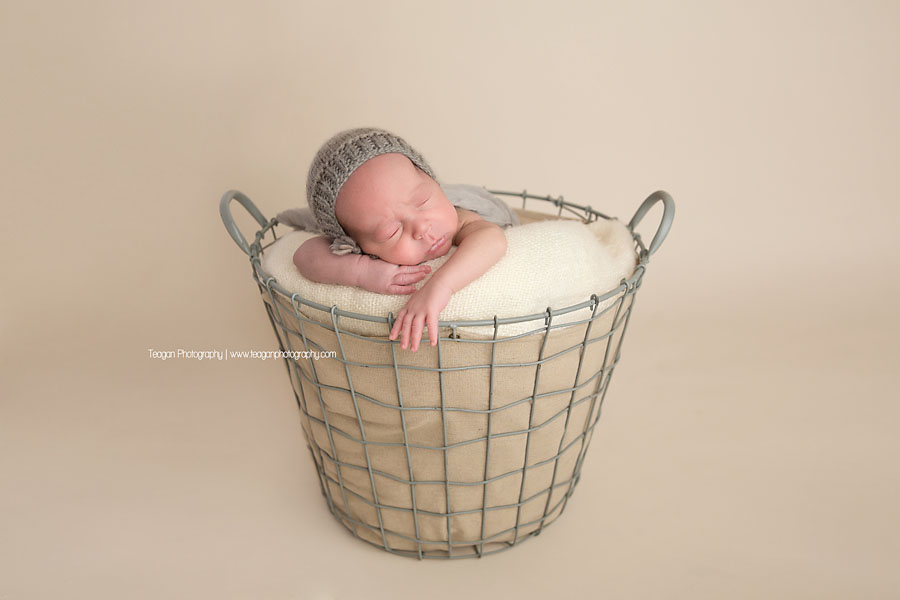 A baby boy in a grey knit hat sleeps soundly during a photography session