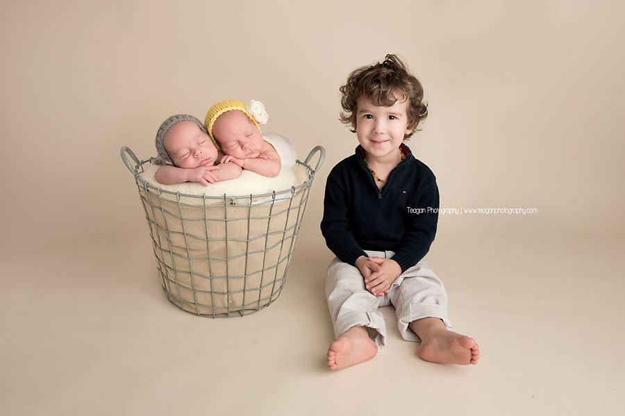 Twin babies snuggle together in a basket while their curly haired big brother sits next to them during an  Edmonton newborn photography session