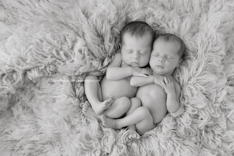 A black and white photo so newborn twin girls snuggled up together