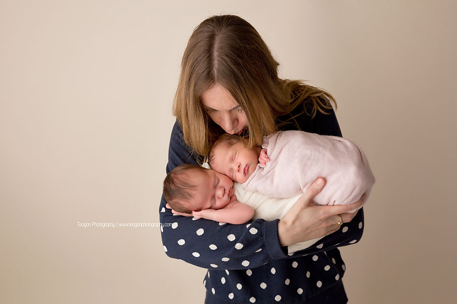 An aunt holds her new nieces during an Edmonton twin newborn photoshoot