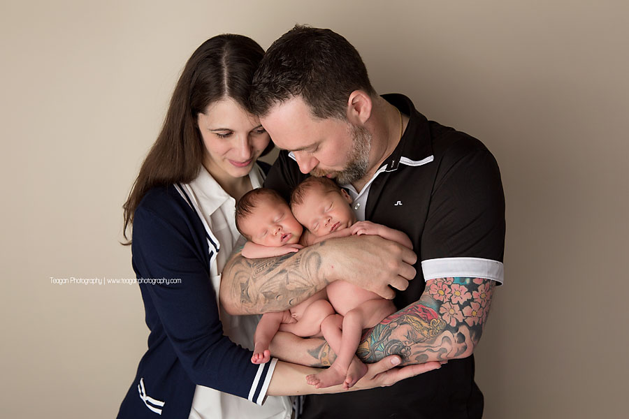 A dark haired couple snuggle together with their newborn twin daughters during an Edmonton photo session