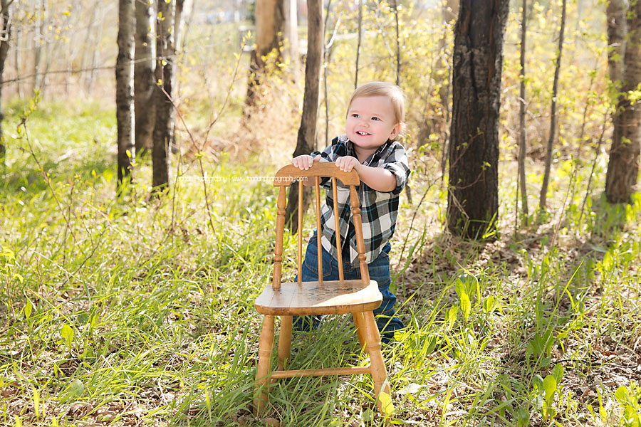 A one year old boy in blue jean overalls poses  with a little chair in the new grass during a Spring photo shoot in Edmonton