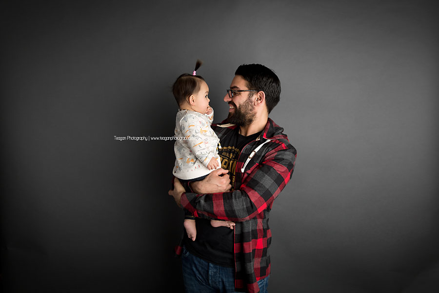 A father and baby daughter wearing red plaid giggle together during an Edmonton daddy and me photo session