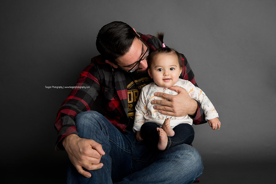 A dark haired man with dark rimmed glasses hugs his chubby baby girl
