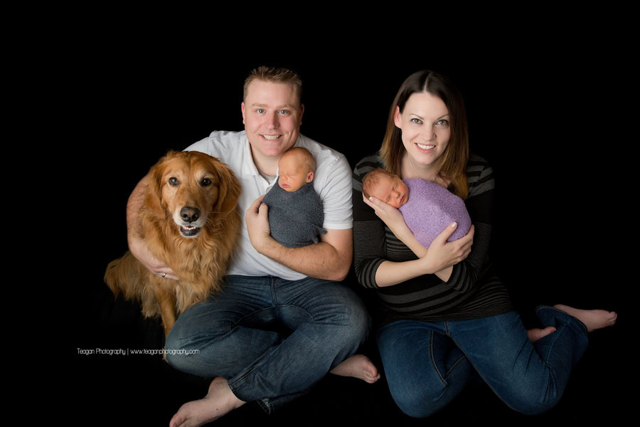 A new mother and father snuggle their twin babies during an Edmonton newborn photo session