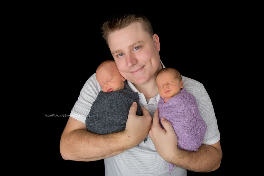 Standing in front of a black backdrop is an Edmonton father holding his twin newborn babies