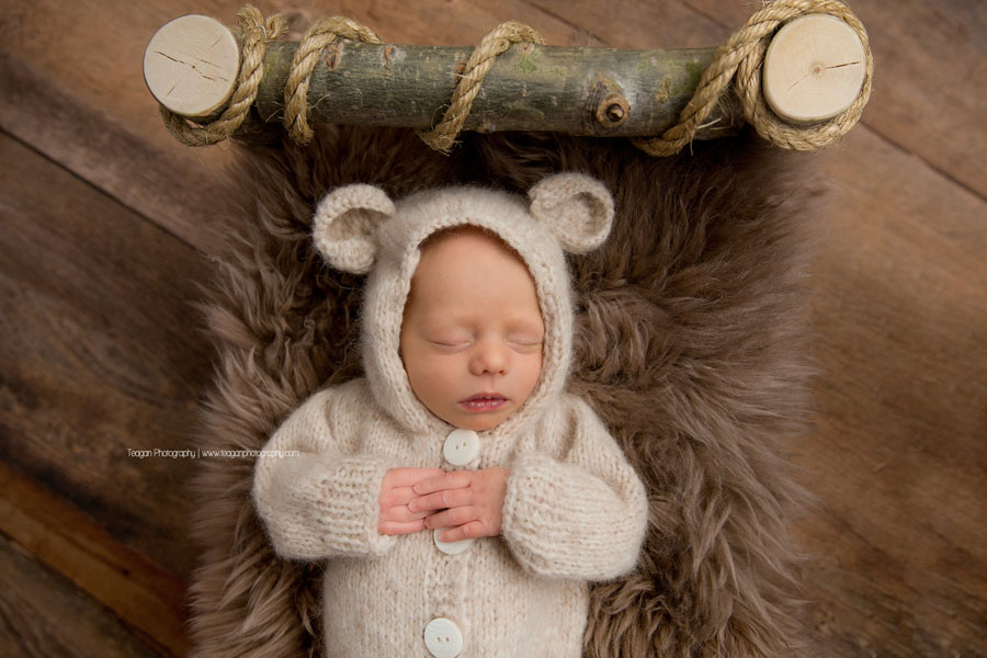 A newborn boy sleeps in a cream coloured teddy bear costume
