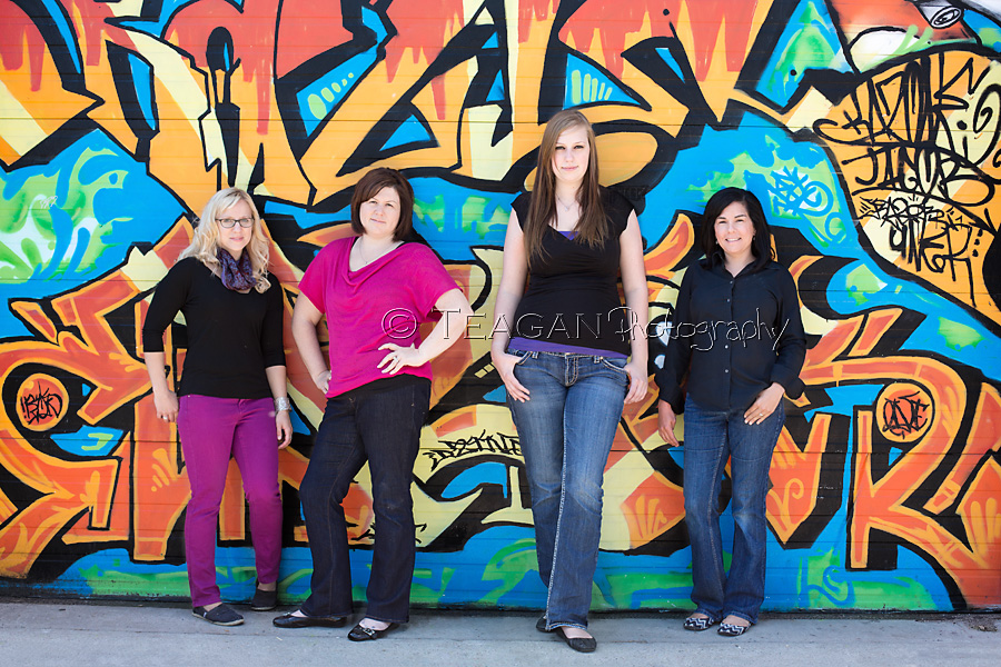 Staff members pose in front of a vibrant graffitii in Old Strathcona for a quick office photo shoot
