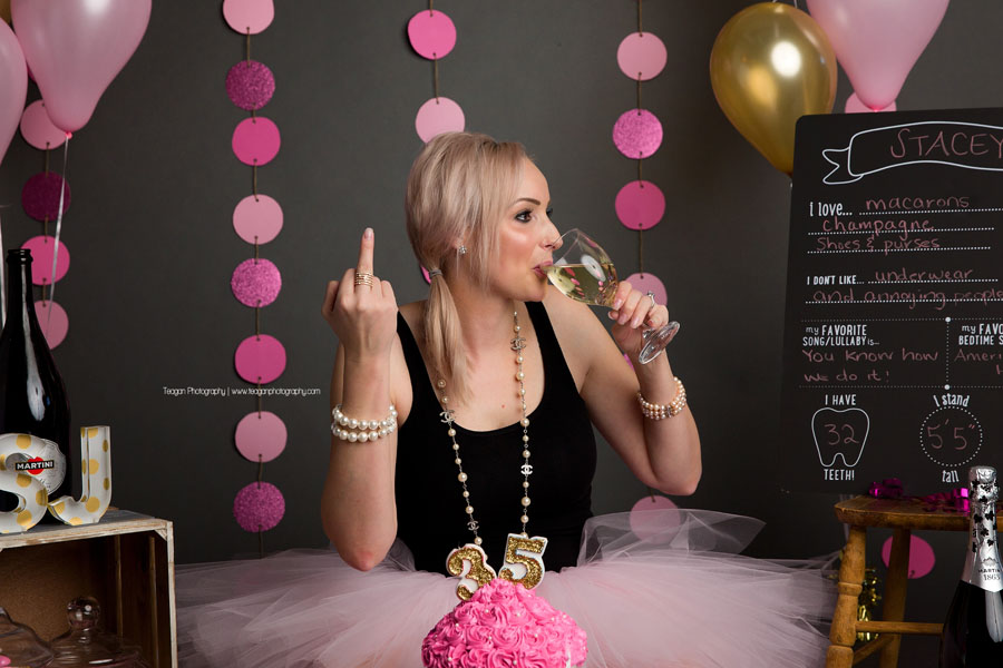 A blonde woman wearing a pink tutu tastes the pink icing on her birthday cake during an adult cake smash photoshoot