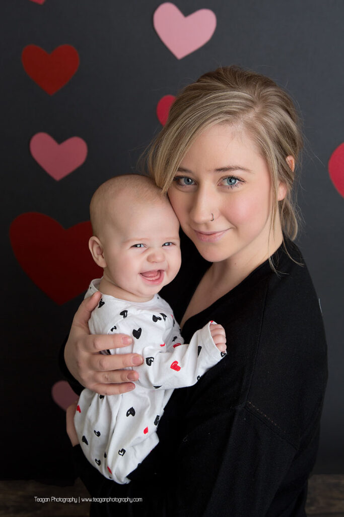 A blond haired mother snuggles with her baby in front of a grey wall covered in hearts