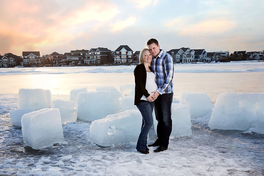 A husband and wife snuggle together in ront of loarge chunks of ice at Lake Summerside in Edmonton during winter maternity photos.
