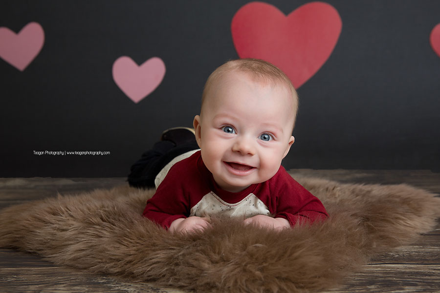 A happy baby boy does tummy time during a Valentine's mini session in Edmonton