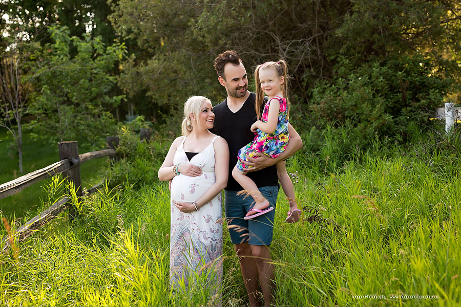 A woman in white smiles at her family during a summer maternity photoshoot in Edmonton