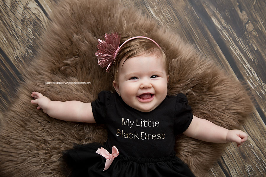 A happy smiling baby in a black dress lays on her back on a brown rug