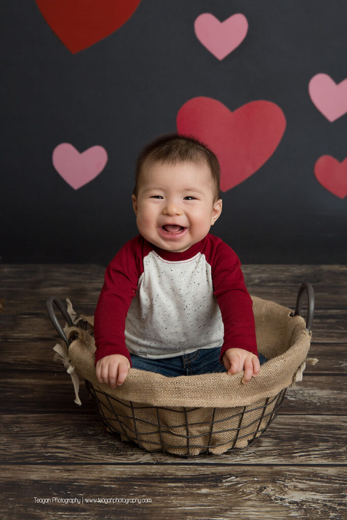 Sitting in a wire basket is a baby girl during a Valentine's Mini photoshoot in Edmonton
